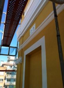 Acabados de pintura en fachada principal de edificio en rehabilitación en Badalona.